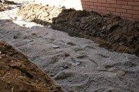 Podsypka piaskowa po korytowaniu z zaznaczonymi poziomami brukowania
